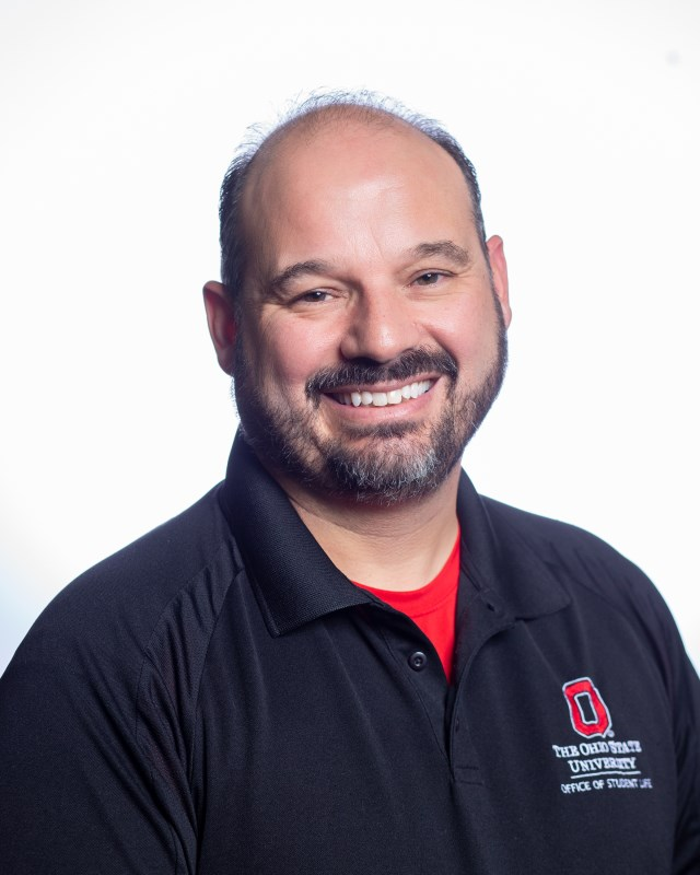 A Photo of Dion Elizondo. A smiling Mexican-American man with a salt and pepper mustache and beard.  He is wearing a black Ohio State University - Office of Student Life polo with a red t-shirt underneath.